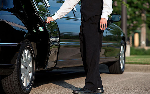 a professional chauffeur opening a door of a limousine